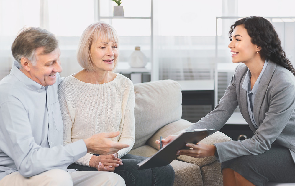 Insurance professional sits with elderly couple to educate them about their risks and options to reduce risk.