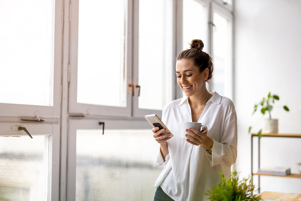 woman holding and smiling at her smartphone