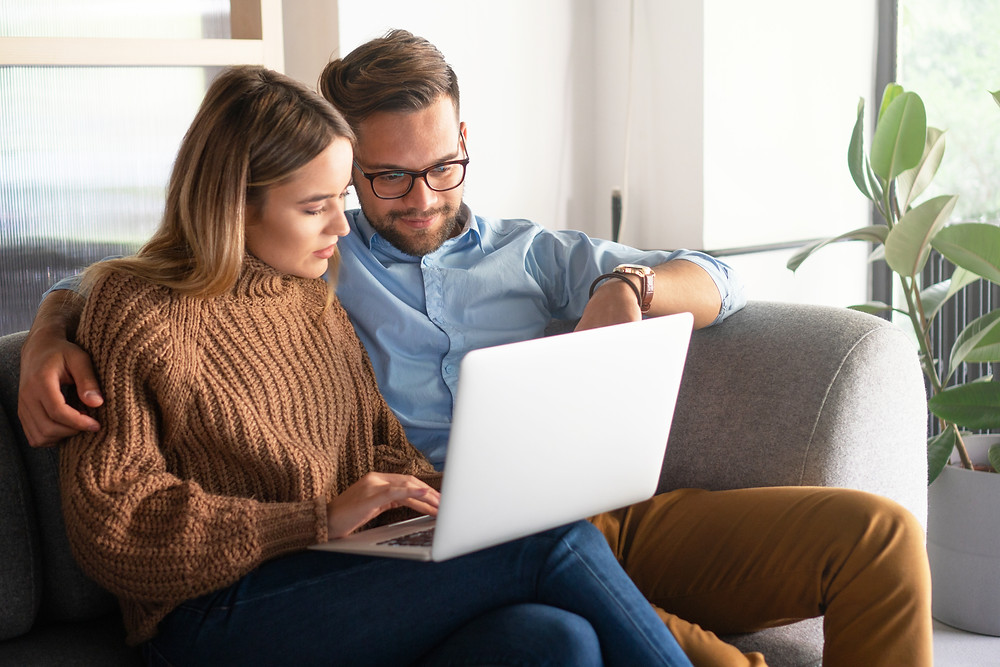 Young couple browses the internet for insurance.
