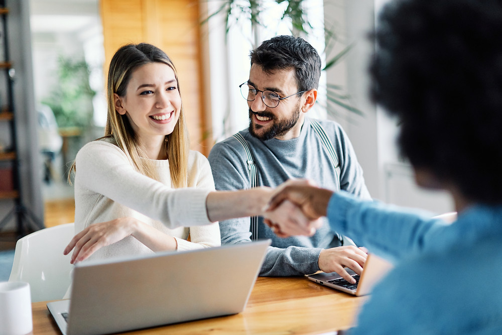 Young couple meets with insurance agent for annual customer insurance review