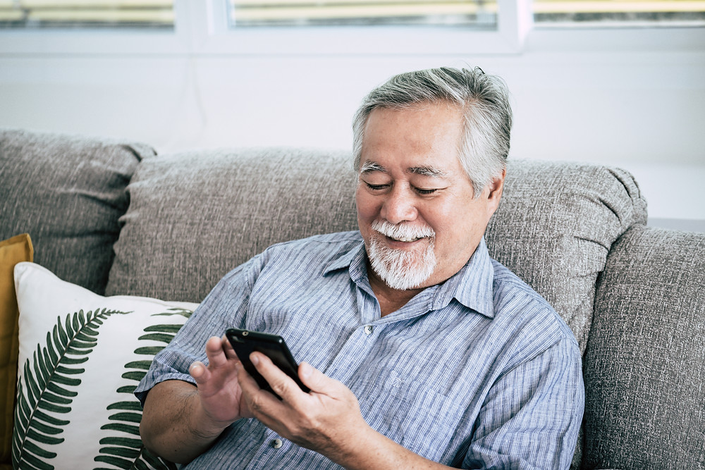 man sitting on couch scrolling on his smart phone