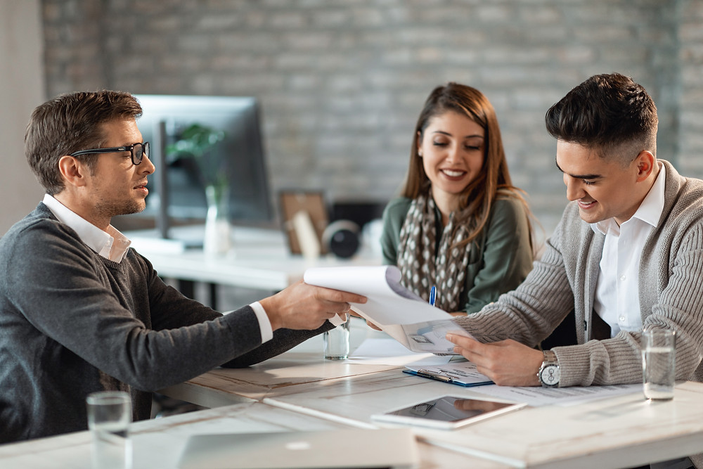 Insurance agent meets with a couple to review their current policies.
