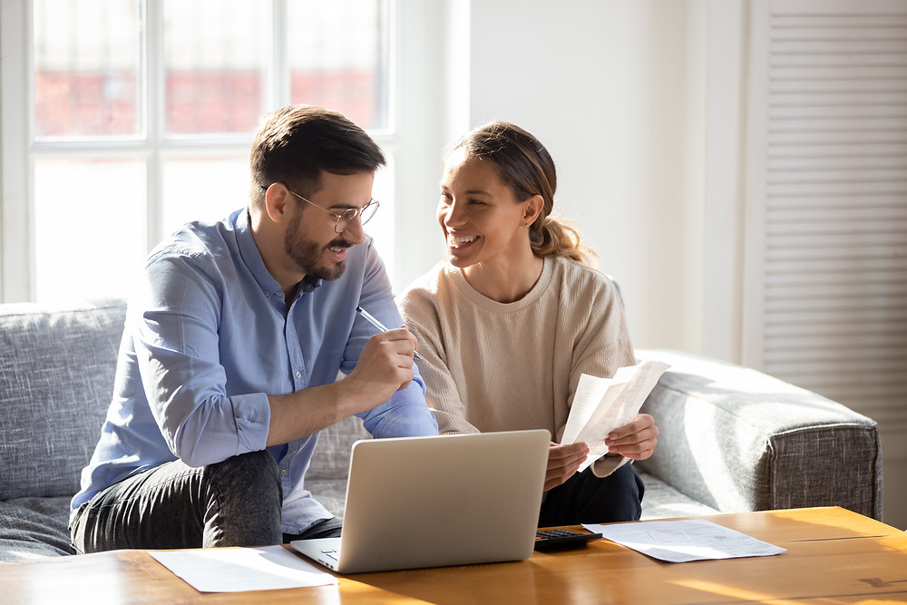 Young couple discusses when they can schedule their insurance review appointment with their agent.