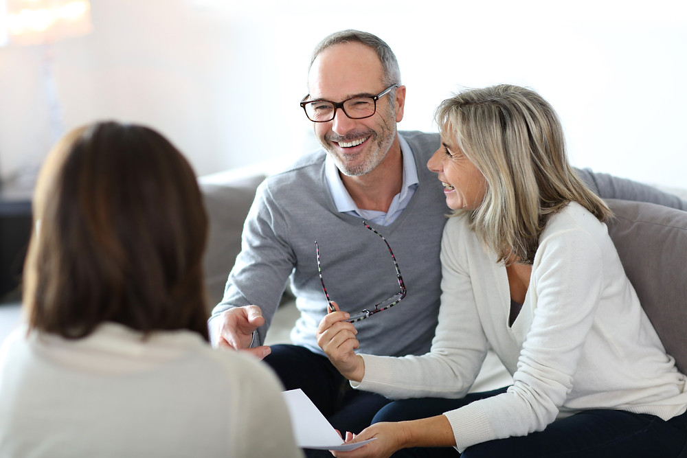 Insurance agent meets with older couple to review their current coverage.