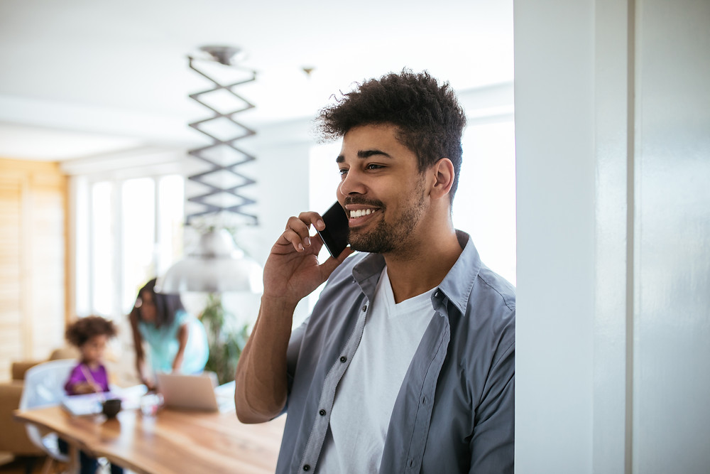 Father stands in kitchen while talking on the phone to set up an insurance review appointment with his agent.