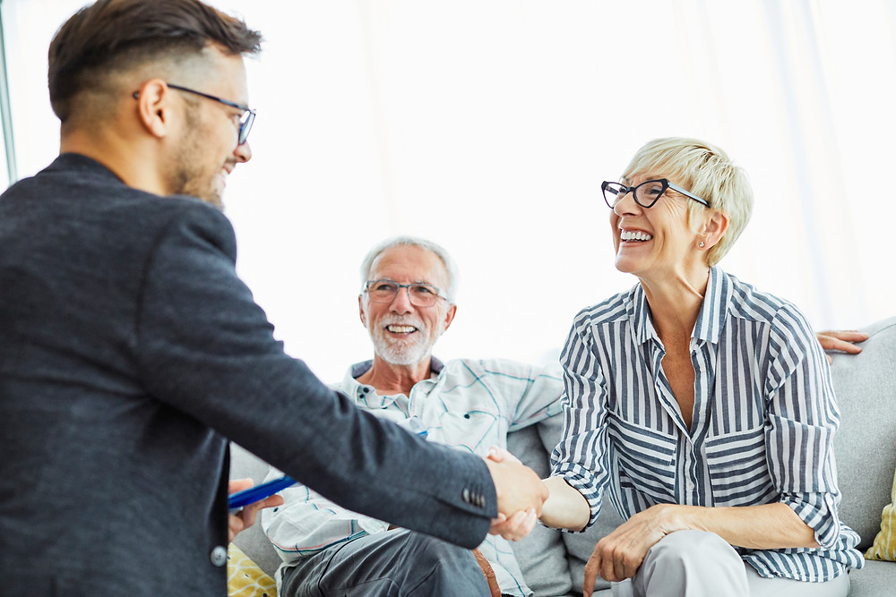 insurance agent sits with elderly couple for a customer insurance review meeting.