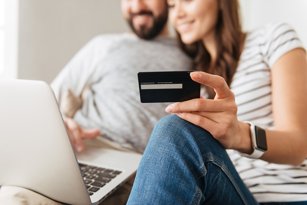 Couple sits on couch and browses the internet for the cheapest insurance options.