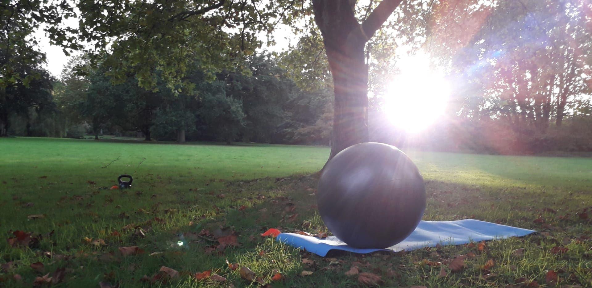Foto: Swiss bal en matje in het Nerompark met een opkomende zon.