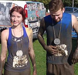 Kelly en haar man na een hinderisserun. Met een medaille rond de nek en vol modder.
