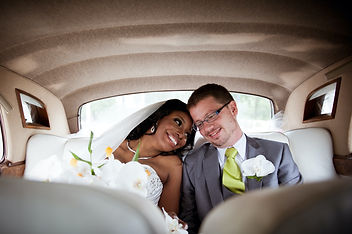 A Just-Married Woman And Man Smile Together As They Sit In The Limo