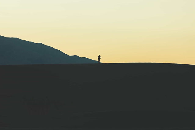 Silhouette Of A Person Standing Atop A Large Hill While Looking At A Mountain In The Distance