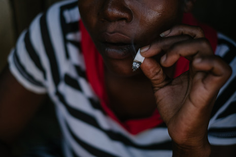 A sex worker smokes a joint in the alley behind a bar hotspot in the centre of Mwanza town, where sex workers rent rooms for clients - In Mwanza and Dedza districts, and Zalewa in Neno district, MSF uses the 'one-stop' clinic approach combined with outreach services targeted towards sex workers who offer their services openly and often work and live together in rented accommodation near transport hubs or at hotspots and bars.  Community health workers – themselves sex workers who have been recruited from their local communities and trained - conduct weekly health promotion sessions at different sites where they provide condoms and lubricant, and facilitate door-to-door HIV testing services (HTS) with a trained counsellor.  The MSF community health workers identify new sex workers or those in need of medical care and navigate them towards MSF's 'one-stop' clinics in nearby Ministry of Health centres in the three sites. Here, MSF clinicians offer a comprehensive package of HIV care plus sexual and reproductive healthcare, all offered in a single visit. MSF has reached approximately 3851 sex workers across these three sites.