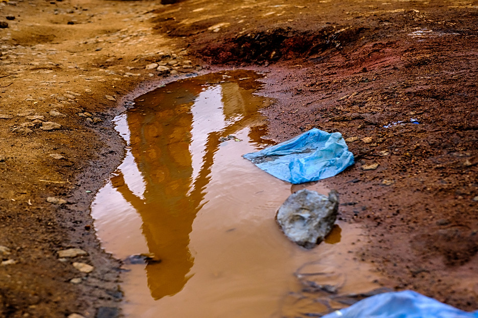 A puddle reflects the outline of a woman outside Dedza district hospital where MSF runs a 'one-stop' clinic for sex workers, where they are offered a comprehensive package of healthcare in one visit.  - In Mwanza and Dedza districts, and Zalewa in Neno district, MSF uses the 'one-stop' clinic approach combined with outreach services targeted towards sex workers who offer their services openly and often work and live together in rented accommodation near transport hubs or at hotspots and bars.   Community health workers – themselves sex workers who have been recruited from their local communities and trained - conduct weekly health promotion sessions at different sites where they provide condoms and lubricant, and facilitate door-to-door HIV testing services (HTS) with a trained counsellor.   The MSF community health workers identify new sex workers or those in need of medical care and navigate them towards MSF's 'one-stop' clinics in nearby Ministry of Health centres in the three sites. Here, MSF clinicians offer a comprehensive package of HIV care plus sexual and reproductive healthcare, all offered in a single visit. MSF has reached approximately 3851 sex workers across these three sites.