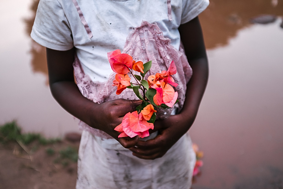 Idiatou, 7 years old, with some flowers in her hand - a metaphor for her sexuality that is endangered by the tradition of female circumcision in Guinea.