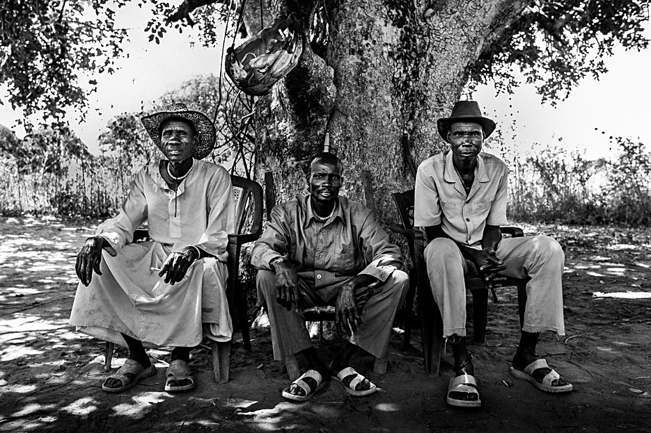 Three leaders of the village Mabok Rual in Gogrial West County. The Dinka culture has a strong hierarchy built around all different kind of leaders. During meetings, men and women are sitting separately and mostly men are speaking. In this village the traditional court is held under this tree.