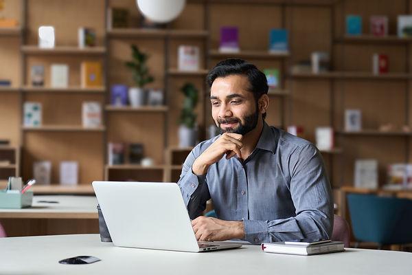 Smiling indian businessman working on la