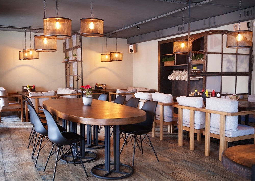 calm cafe with wood floor, orange lights, aesthetic cafe and coffee shop, suitable for meetings, social gatherings and chilling with friends, rustic decorations in cafe, warm vibes