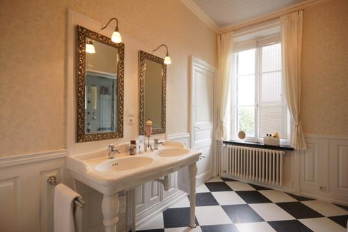 Badkamer met dubbele douchecabine/wasbakken en toilet