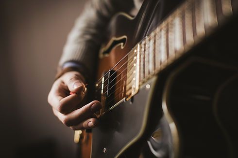spielt eine Gitarre