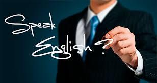 """Pessoa escrevendo """"Speak English?"""" em uma lousa de vidro"""
