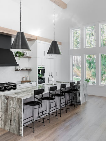 Renovated, contemporary white kitchen with light fixtures, and white cabinets in Langley B.C.