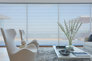 Silhouette sheers and shadings in a living room with two white chairs and a white table.