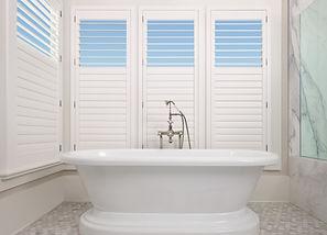 Palm beach shutters in a white bathroom.