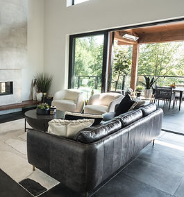 Cropped image of a styled living room with a grey sofa and two white chairs.