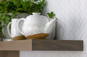 Cropped image of a white and brown ceramic tea pot on a wooden floating shelf.