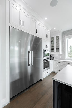 Large two door Miele refridgerator and white cabinets.