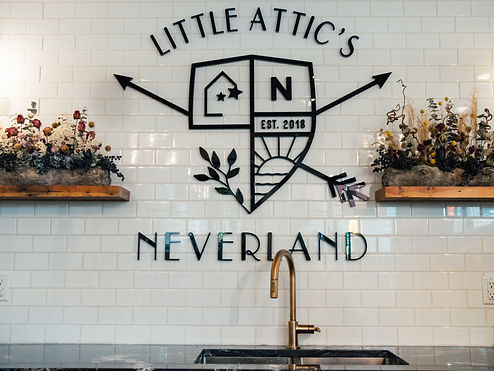 Little Attic's Neverland sign, white tiles, and faucet.