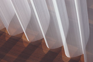 Shadows of the sheers and shadings on the wooden floor.