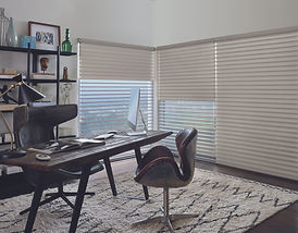 Hunter Douglas blinds in an office with a brown chair and brown table.