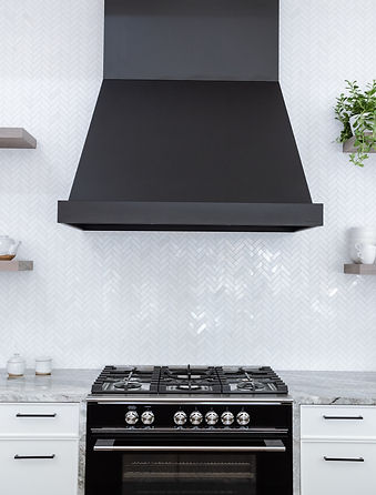 Close up of the black kitchen hood and black fisher and paykel oven.