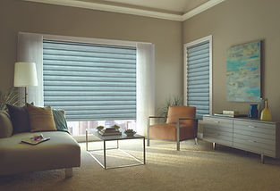 Solera roman shades in a living room with orange chair and grey table.