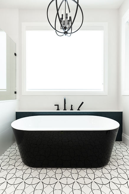 Black and white bathtub, large window, and black spherical light fixture in the ensuite.