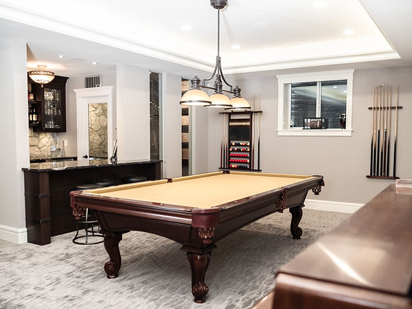 Pool table, light fixtures, and bar in the basement.