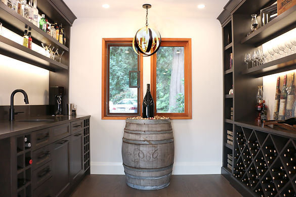 Wine room with wine rack, dark brown cabinets, and wine barrel.
