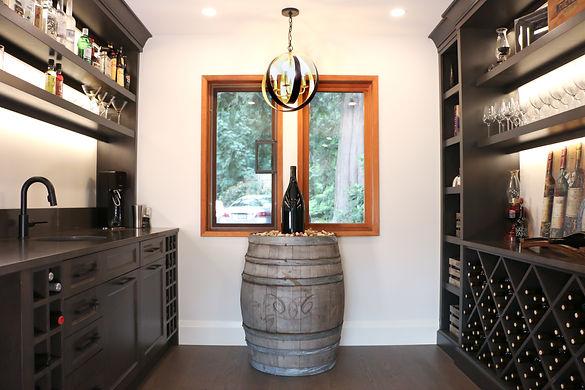 Wine room with wine rack, dark brown cabinets, and wine barrel.
