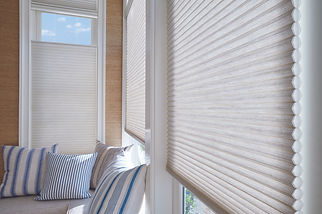 Duette cellular honeycomb shades with blue and white pillows.