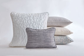 Large, white pillow, small grey pillows, tan pillow, and green pillow.