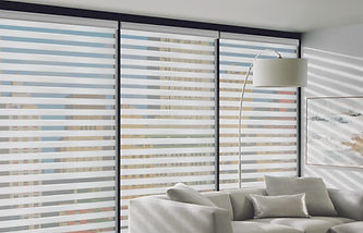 Designer banded shades in a living room with a white sofa and white lamp.
