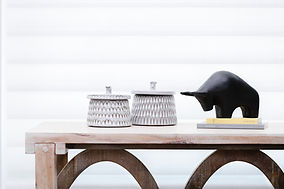 Cropped image of ceramic boxes and black raging bull on a mercana contemporary console table.