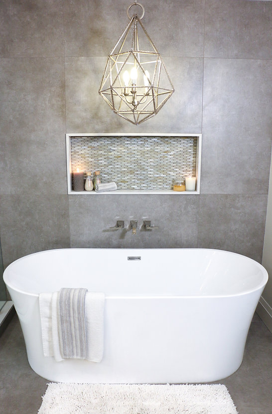 White bathtub with hanging light fixture and wall mount faucet.