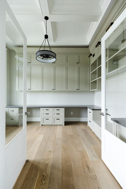The office with double door entrance, circular light fixture, and light green cabinets.