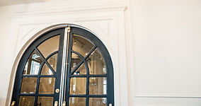 Cropped image of antique arched, black doors in Vancouver B.C.