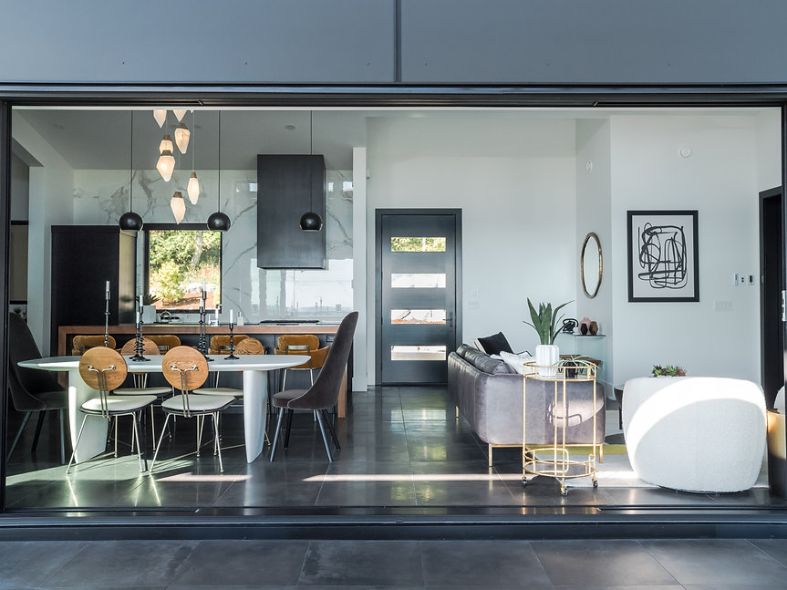 Cropped banner image of a modern home with a black door, black light fixtures, and black cabinets.