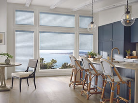 Sonnette roller and solar shades in a kitchen with chairs and blue cabinets.