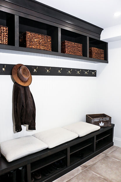Mudroom bench with white pillows on top and hat and jacket hanging on the hook.