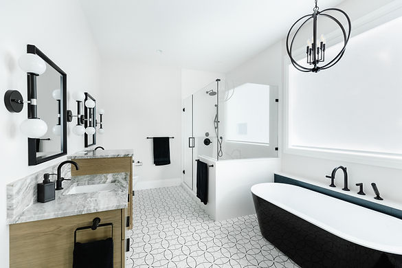 Ensuite with glass shower doors, black and white bathtub, and patterned tiles.